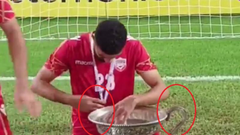 لاعبو البحرين يكسرون الكأس بعد فوزهم به